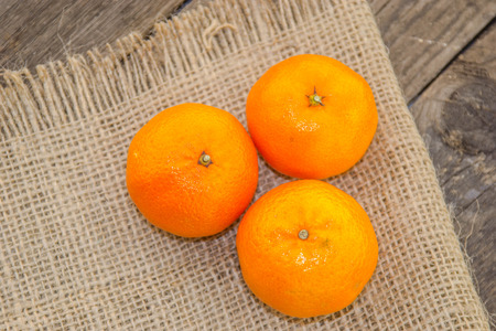 Clementines on a jute base with a wooden table Stock Photo
