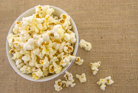 Fresh, delicious hand-popping popcorn in a bowl on a rustic jute base