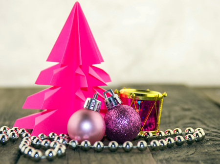 Christmas decoration with origami Christmas tree pink and bright pink balls and silver beads Stock Photo