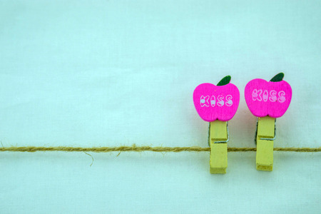 Two wooden apple-shaped clippers, hung on a rope. Isolated on a white background.