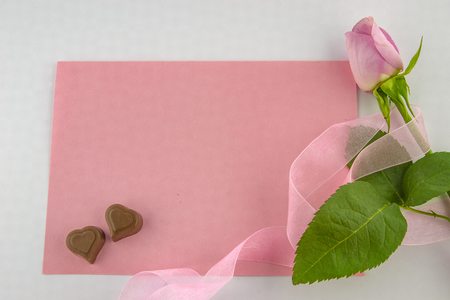 International Women's Day, March 8. Blank pink card with a pink rose wrapped in a decorative pink ribbon and two chocolate-shaped hearts on a white background. Stock Photo