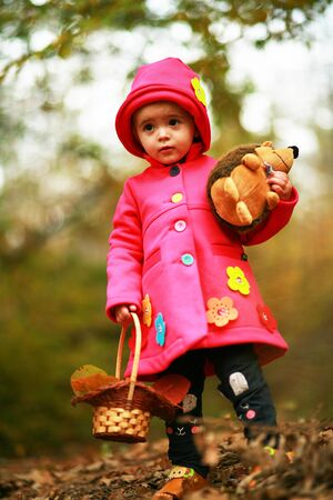 A little girl is standing as little red riding hood in the forest , holding her toy with scared look. Halloween costume concept 写真素材