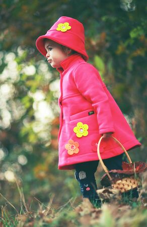 Portrait of Little red riding hood in modern clothes holding her basket. Small girl with worried,sad look concept 写真素材