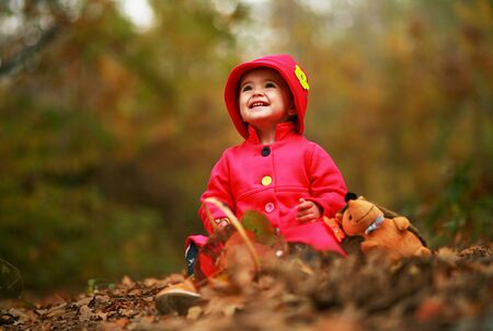 Portrait of cute girl dressed as red riding hood for Halloween, smiling wide while sitting in pile of leafs in the forest