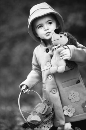 Beautiful girl and her doll lost in the forest in black and white . Red riding hood fairy tale concept 写真素材