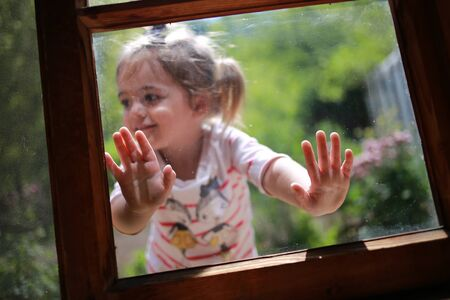 Happy kid with hands on window glass, looking sideways smiling in summer day with blurred background