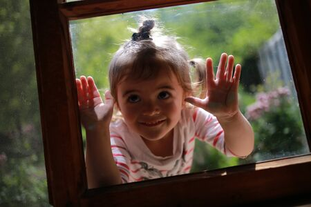 Happy blonde girl with hands on window glass, looking through the window to see what is inside