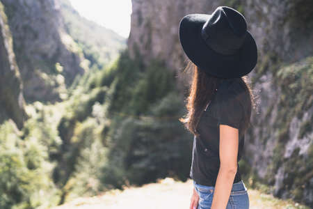 Young european female tourist with black hat watching Devils Throat Cave, Bulgaria