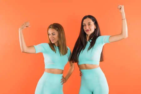 Young fit athletic women flexing their arm muscles and smiling