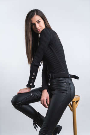 Portrait of stylish Beautiful woman in black clothes and high boots sitting on a char