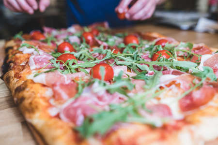 Chef hands preparing large pizza on wooden table. Preparing Parmesan, bacon, arugula pizza at restaurant