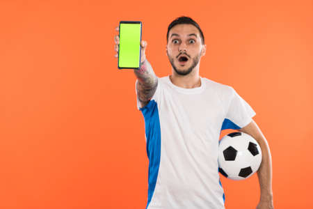 Amazed soccer fan with ball in his hand or player show green screen phone