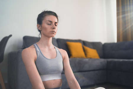 Close look of meditating woman in grey sportswear sitting on floor at home