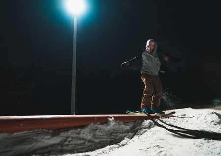 Freestyle skier hitting the rail at snow park in ski resort at night