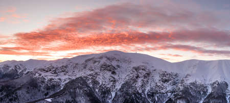 Panoramic view of snowy mountain peaks and red sunset colors