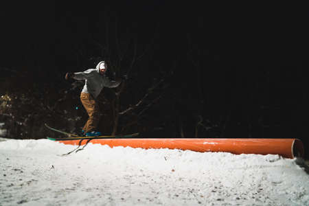 Skier going down a rail at public park in the night