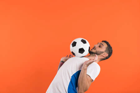 Concentrated football player in white blue shirt doing tricks with soccer ball, isolated on orange background
