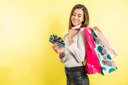 Pretty woman holding credit cards and shopping bags