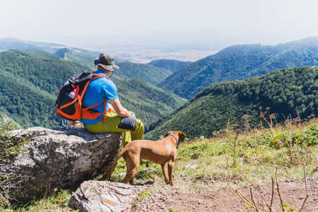 A young hiker and his Vizsla dog hiking to the top of a mountain