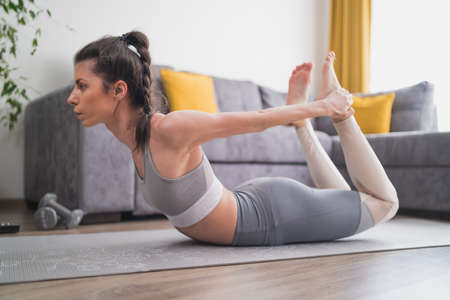 Young beautiful woman practicing yoga, lying in Bow pose on yoga mat at home