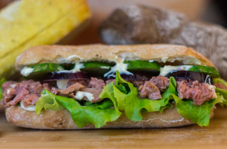 Tuna sandwich, with red onions, sallad and cucumber slices, moving around on a wooden table