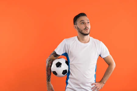 Football player holding a ball isolated on orange background Banco de Imagens