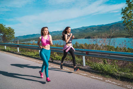 Two female sport models running on asphalt road near lake outdoors