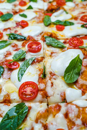 Close up of sliced Pizza with tomatoes, mozzarella cheese and fresh green basil