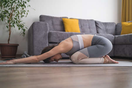 Side view of fit girl in gray sportswear doing morning yoga practice at home. Balasana pose