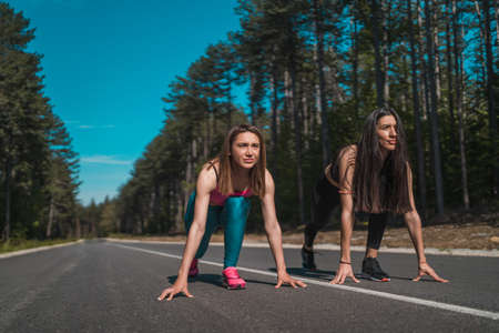 Fit female runners ready to go in a challenge outdoors on an asphalt road