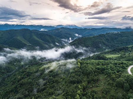 Epic green landscape forest in the spring. Mountain range in Bulgaria in cloudy fog day