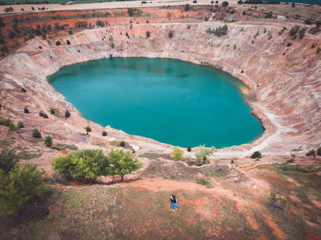 Aerial view of couple on travel adventure at abandoned open mine pit