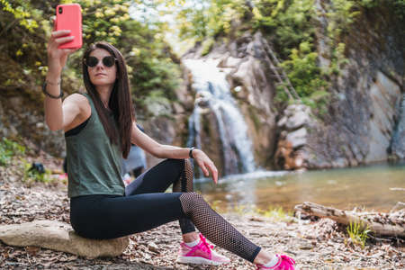 Girl taking selfies with pink phone near waterfall in the forest Banco de Imagens