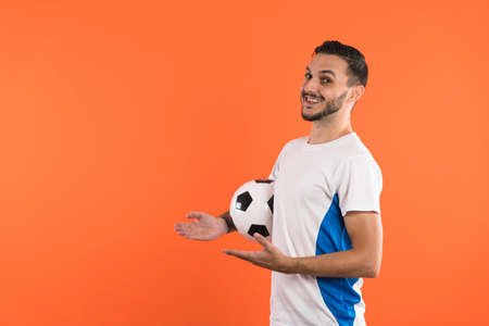 Happy smiling Football fan or player presenting a product on the left with open hands Banco de Imagens