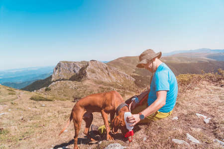 Adventurous Hiker and his hungarian vizsla dog are taking a rest at the top of the mountain drinking water