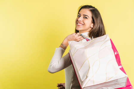 Smiling woman looking on side with shopping bags over shoulder Banco de Imagens