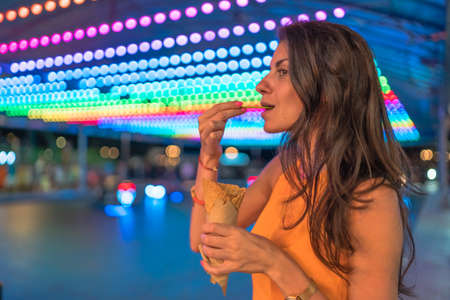 Portrait of happy woman eating ice cream with waffle cone at the carnival with colorful lights in the background