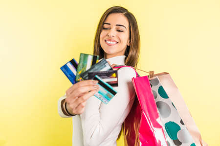 Smiling woman with shopping bags holding set of fanned-out credit cards in front her Banco de Imagens