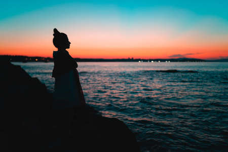 Silhouette Of Beautiful Young Woman Profile Looking at the Sea at Sunset with sea horizon in the background