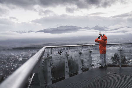 Back view of man with orange jacket taking photos of misty mountains in Razlog city Banco de Imagens