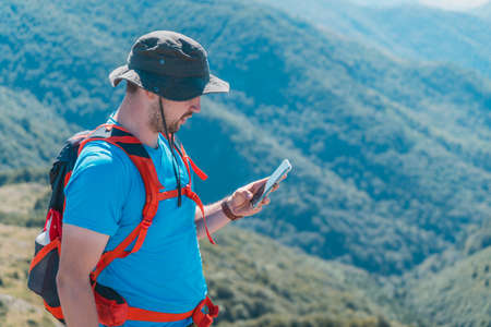 Man checking GPS while on a hiking trip in the mountains