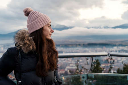 Portrait of Smiling woman enjoying the view of city under misty snowy mountains