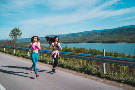 Sports young girls jogging near scenic lake. Active lifestyle girls workout