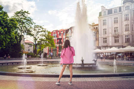 Back view of woman watching beautiful fountain in Plovdiv, European capital of culture