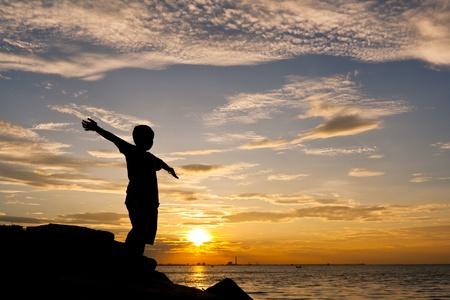 aire puro: Feliz niño de pie en la costa de piedra Foto de archivo