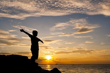 Happy boy standing on coast stone