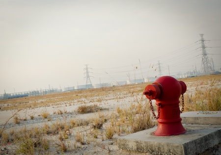 Red fire hydrant stand alone at dry field of power plant