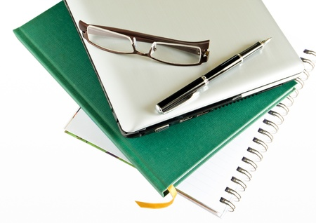 Glasses and Laptop on Stack of Books