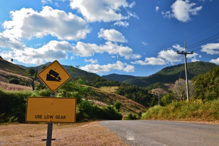 Steep road sign and rural landscape with hills and mountains in eastern Thailand