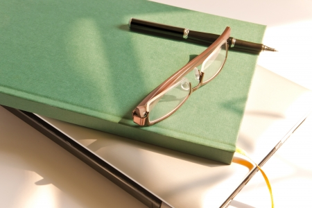 Glasses and Books on Stack of Laptop